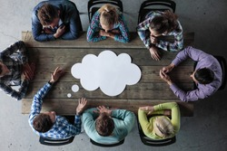 Hipster business teamwork brainstorming planning meeting concept, man tells his opinion, people sitting around the table with white paper shaped like dialog cloud