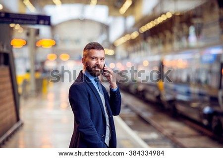 Hipster businessman with smartphone, making a phone call, platfo #384334984