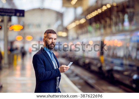 Hipster businessman with smartphone, waiting, train platform #387622696