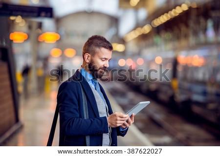 Hipster businessman with tablet, waiting, train platform #387622027