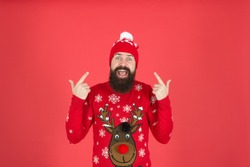 Hipster cheerful bearded man wear winter sweater and hat. Happy new year. Join holiday party craze and host ugly christmas sweater party. Feeling awesome. Buy festive clothing. Sweater with deer.