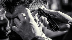 Hipster client getting haircut. Hands of barber with hair clipper, close up. Haircut concept. Man visiting hairstylist in barbershop. Barber works with hair clipper. Black and white.
