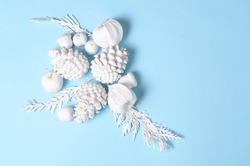 Hipster conceptual minimalist christmas and new year background. Pine cones and branches, physalis flowers. White objects on a blue background with space for greeting text
