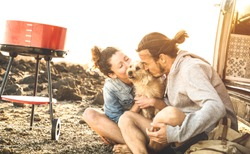 Hipster couple and cute dog relaxing by travel on oldtimer mini van transport - Wander lifestyle concept with indy people on minivan adventure trip having fun at barbecue moment - Warm sunshine filter