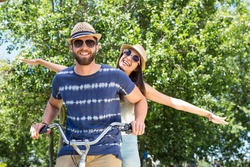 Hipster couple on a bike ride in the park on a summers day
