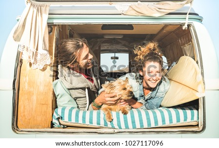 Hipster couple with cute dog traveling together on vintage mini van transport - Life inspiration concept with hippie people on minivan adventure trip in relax moment - Bright warm retro filter