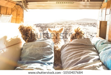 Hipster couple with cute dog traveling together on vintage van transport - Life inspiration concept with hippie people on minivan adventure trip watching sunset in love moment - Warm sunshine filter #1050407684