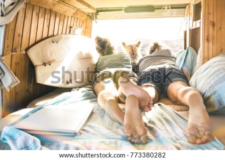 Hipster couple with cute dog traveling together on vintage van transport - Life inspiration concept with hippie people on minivan adventure trip watching sunset in relax moment - Warm sunshine filter #773380282