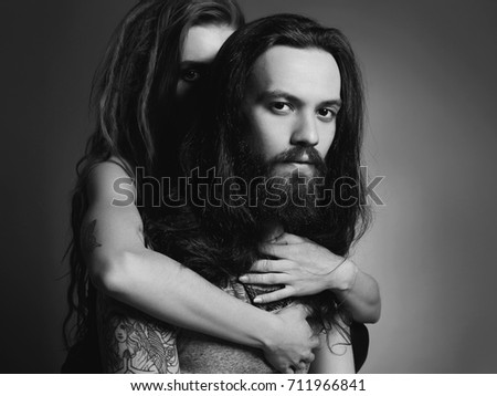Stock Photo hipster couple with tattoo.beauty woman and bearded man in hugs.boy with tattoo and girl with dreadlocks