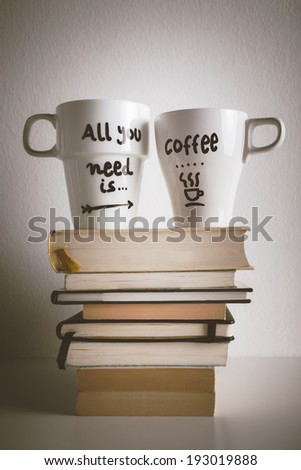 Hipster cup of coffee over a books./ Two white coffee mug with diy decoration on vintage effect.