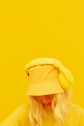 Hipster Dj Girl posing in studio. Urban style. Hip-hop, dancer.Trendy casual outfit. Bucket hat Fashion yellow monochrome aesthetic colours.