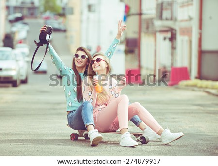 Hipster fashion girlfriends taking a self photo in urban city context seat on skate keep moment with modern digital camera