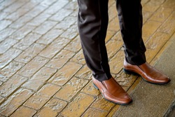 Hipster fashion man's legs in black jeans and brown leather boots on wooden floor