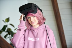 Hipster fashion woman with pink hair wears vr glasses headset holds controller looks at camera. Digital innovation video gaming, virtual reality 3D 360 experience concept. Head shot face portrait.