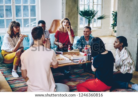 Hipster friends gathering eating pizza and spending weekends time together at home interior in friendly company.Young multicultural people dressed in casual wear have party in modern apartment