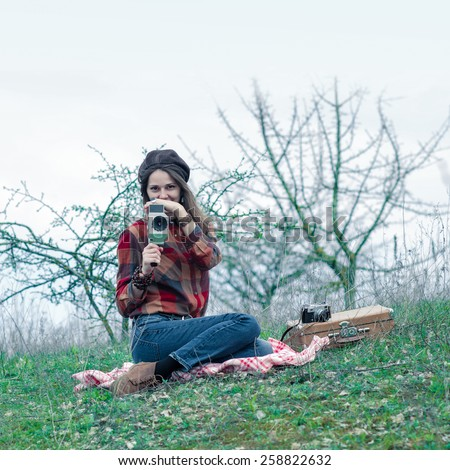 Hipster girl in a plaid shirt makes movies on a vintage movie camera.