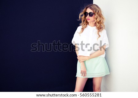Hipster Girl in and Sunglasses on Contrasted Black and White Wall Background. Urban Fashion Woman Outdoors in Summer. Trendy Street Style Female in Skirt and Blouse. Toned Photo with Copy Space.