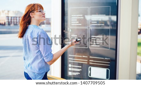 Hipster girl in spectacles for provide eyes protection pondering on information checked on billboard with advertising text about mobile application with touristic guide, woman on publicity area