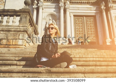 Hipster girl in sunglasses is looking away, while is sitting with touch pad against old architectural building. Young woman tourist is holding digital tablet, while is resting after tour in museum