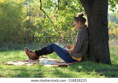 Hipster girl leaning on a tree and using tablet computer
