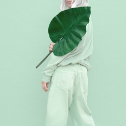 Hipster Girl posing in studio. Urban style. Fresh casual mint outfit. Fashion monochrome aesthetic colours.  Bio palm tropical mood