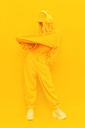 Hipster Girl posing in studio. Urban style. Hip-hop, dancer.Trendy Fresh casual outfit. Fashion yellow monochrome aesthetic colours.