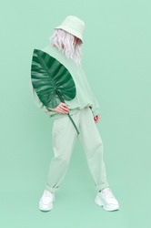 Hipster girl posing in studio. Urban style. Hip-hop. Dancer. Trendy Fresh outfit. Fashion mint monochrome aesthetic colours.