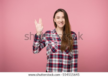 hipster girl showing spock gesture over pink background isolated