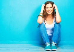 Hipster girl sitting on floor against blue background.