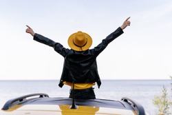 Hipster Girl Sitting on Yellow Car Roof Back View. Woman with Raised Arms at Ocean Summer Freedom Concept. Trendy Female Enjoy Roadtrip Nature River or Lake from Top of Vehicle. Weekend Lifestyle