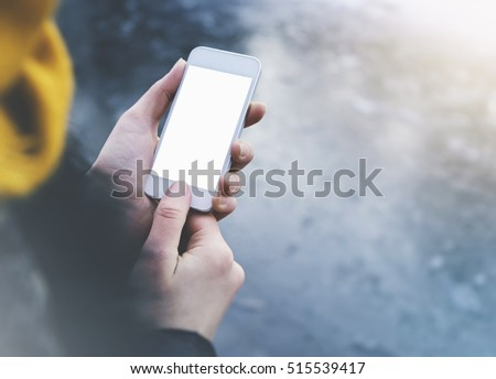 Hipster girl texting message on smartphone mobile in winter nature, view tourist hands using gadget phone on background blue ice and freeze; finger touch screen blank cellphone mockup, templates