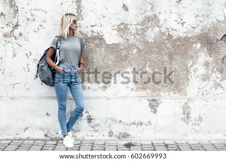 Hipster girl wearing blank gray t-shirt, jeans and backpack posing against rough street wall, minimalist urban clothing style, mockup for tshirt print store - Shutterstock ID 602669993