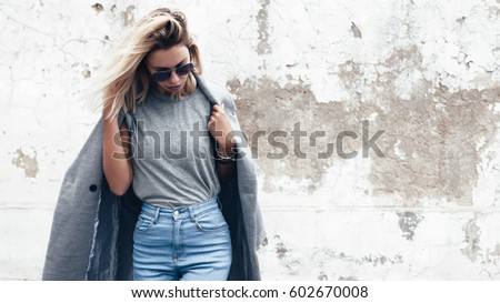 Hipster girl wearing blank gray t-shirt, jeans and coat posing against rough street wall, minimalist urban clothing style, mock up for tshirt print store #602670008