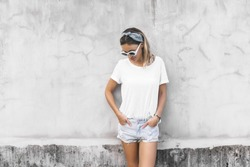 Hipster girl wearing blank white t-shirt and denim shorts posing against gray street wall, blank mockup for tshirt print store