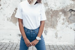 Hipster girl wearing blank white t-shirt and jeans posing against rough street wall, minimalist urban clothing style, mockup for tshirt print store