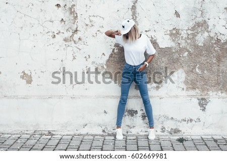 Hipster girl wearing blank white t-shirt, jeans and baseball cap posing against rough street wall, full length portrait, minimalist urban clothing style, mockup for tshirt print store