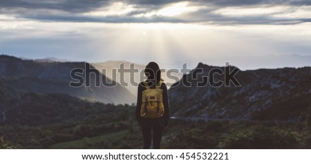 Hipster girl with backpack enjoying sunset on peak foggy mountain. Tourist traveler on background valley landscape view mockup. Hiker looking sunlight in trip Northern Spain Picos de Europa mock up