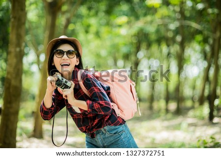 Hipster girl with backpack hold an old camera enjoying of beautiful nature,wanderlust travel concept, space for text,Travel photographers are happy to enjoy traveling in the tropical Asian forests. #1327372751