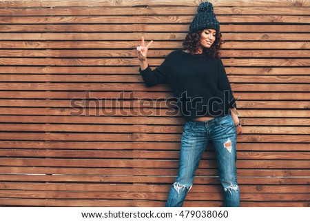Hipster girl with curly hair wearing black sweater, hat and jeans posing against wooden wall, swag street style, autumn outfit