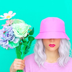 Hipster girl with flowers in trendy bucket hat. Fresh summer vibes. Pastel colours lovers