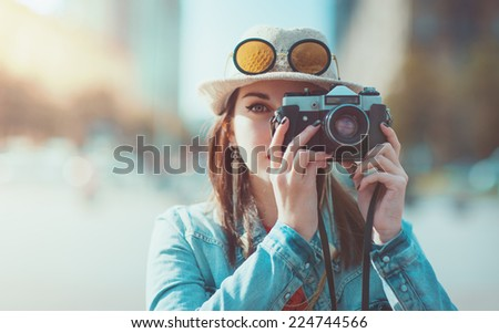 Hipster girl with retro camera. Focus on camera