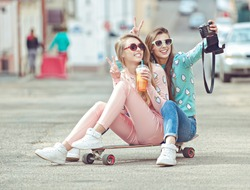 Hipster girlfriends taking a self photo on the street seating on skateboard  in fashion clothes eternalizing the moment with modern digital camera