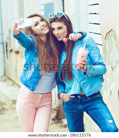 Hipster girlfriends taking a selfie in urban city context. Concept of friendship and fun with new trends and technology. Best friends eternalizing the moment with modern smartphone