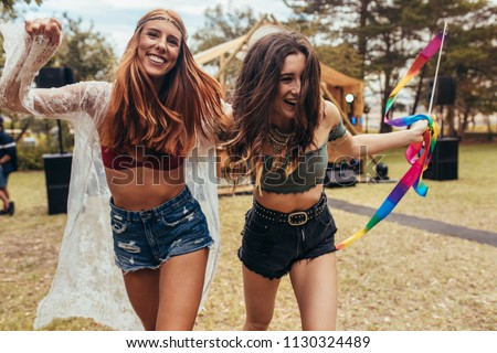 Hipster girls having fun at music festival outdoors. Two women enjoying at park during a summer festival. #1130324489