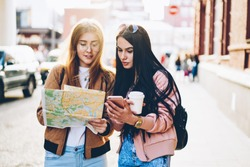 Hipster girls in casual outfit looking at map and searching destination standing in center city during weekend trip.Travellers with online navigator on modern telephone checking rout walking outdoors
