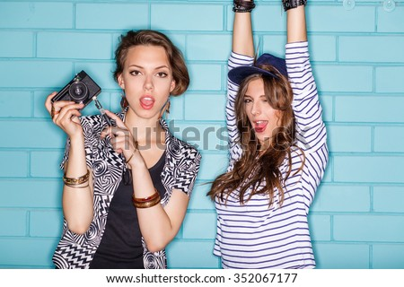 Hipster girls wearing stylish bright outfits going crazy and having great time. Standing together near blue brick wall with photo camera and have fun while taking selfie self portrait of each other.