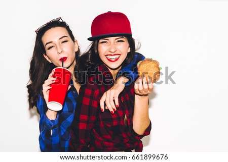 Hipster girls with vegetarian burger drinking a cocktail from straw and having fun, happy, smile and laugh on the white background. #661899676
