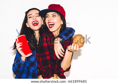 Hipster girls with vegetarian burger drinking a cocktail from straw and having fun, happy, smile and laugh on the white background. #661899685
