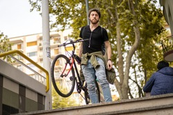 Hipster guy going downstairs to the underground metro station carrying his bicycle
