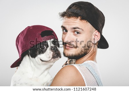 Hipster guy hugging his nice French Bulldog dog against neutral background
